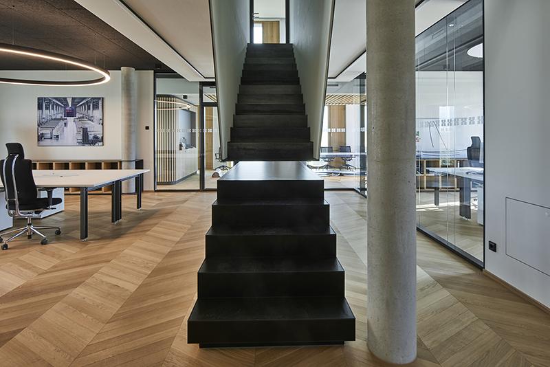 Eine scheinbar unterbrochene Treppe von den Fachabteilungen in das Stockwerk zur Planungsabteilung schließt sich beim Betreten und schafft Verbindung.